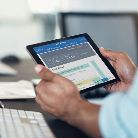 User holding tablet with simPRO timesheets visible